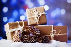 Met de hand gemaakte giftvakjes van ambachtdocument over sneeuw houten lijst in blauw licht Stock Foto