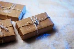 Met de hand gemaakte giftvakjes van ambachtdocument over sneeuw houten lijst in blauw licht Stock Afbeeldingen