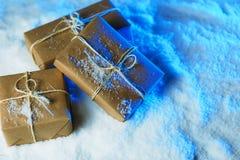 Met de hand gemaakte giftvakjes van ambachtdocument over sneeuw houten lijst in blauw licht Royalty-vrije Stock Afbeeldingen