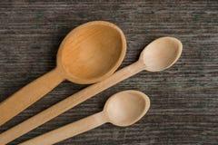 Met de hand gemaakte houten lepels op een houten raad, keukengereedschap Stock Fotografie