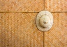 Met de hand gemaakte houten rieten die hoed op een patroon geweven bedelaars als achtergrond wordt gehangen Royalty-vrije Stock Foto's
