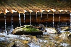 Met de hand gemaakte houten waterafvoerkanalen van kleine behandelde stralen Een mooi fragment van een kleine waterval royalty-vrije stock foto