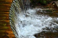 Met de hand gemaakte houten waterafvoerkanalen van kleine behandelde stralen Een mooi fragment van een kleine waterval royalty-vrije stock afbeelding