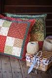 Met de hand gemaakte lapwerkkussens met het naaien van hulpmiddelen op houten lijst Stock Fotografie