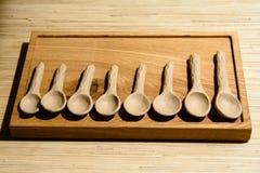 Met de hand gemaakte lepels op een houten raad Stock Foto