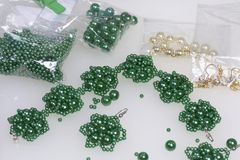 Met de hand gemaakte oorringen en armband Handwerk thuis Pareljuwelen Groene kleur Op een witte achtergrond De parels zijn dichtb Stock Fotografie