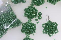 Met de hand gemaakte oorringen en armband Handwerk thuis Pareljuwelen Groene kleur Op een witte achtergrond De parels zijn dichtb Royalty-vrije Stock Foto's