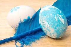 Met de hand gemaakte paaseieren en blauwe die veren op houten backgr worden geïsoleerd Stock Foto's