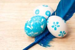 Met de hand gemaakte paaseieren en blauwe die veren op houten backgr worden geïsoleerd Royalty-vrije Stock Foto