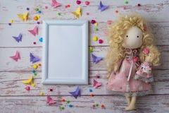 Met de hand gemaakte stoffenpop met kleurrijke parels, document vlinders en wit fotokader royalty-vrije stock foto's