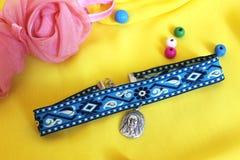 Met de hand gemaakte toebehoren blauwe nauwsluitende halsketting met een zilveren tegenhanger op een gele achtergrond Stock Foto's