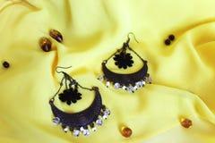 Met de hand gemaakte toebehoren Met de hand gemaakte oorringen met zwarte bloemen op een gele achtergrond Stock Fotografie