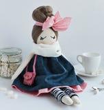 Met de hand gemaakte voddenpop met bleke leuke roze boog stock afbeelding