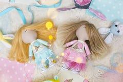 Met de hand gemaakte voddenpoppen met lang eerlijk haar gekleed in lichtblauwe en roze kleding met roomijs Royalty-vrije Stock Foto's