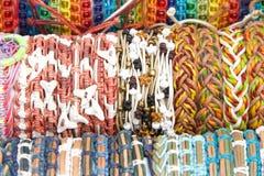 Met de hand gemaakte vriendschapsarmbanden in diverse die kleuren en patronen in rijen worden opgesteld Royalty-vrije Stock Afbeelding