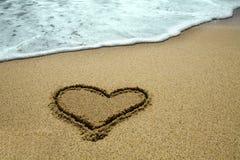 Met de hand geschreven hart op zand stock fotografie