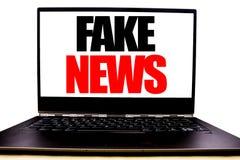 Met de hand geschreven tekst die Vals Nieuws tonen Bedrijfsconcept die die voor Hoax Journalistiek schrijven op het monitor voors royalty-vrije stock afbeelding
