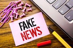 Met de hand geschreven tekst die Vals Nieuws tonen Bedrijfsdieconcept voor Hoax Journalistiek op roze kleverig notadocument wordt stock afbeelding