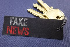 Met de hand geschreven tekst die Vals Nieuws tonen Het bedrijfsconcept die die voor Hoax Journalistiek schrijven op notadocument  royalty-vrije stock foto's