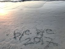 """Met de hand geschreven woorden """"bye tot ziens 2017† op het strand met vele voetafdrukken royalty-vrije stock foto"""