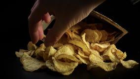 Met de hand plukkend heerlijke chips - Ongezonde kost stock videobeelden