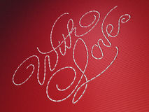 Met de woorden van het liefdeborduurwerk op rood Stock Foto