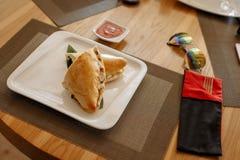 Met? della pizza di Calzone sullo strato di bamb? in piatto quadrato sulla tavola di legno immagini stock libere da diritti