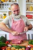 Metà di colpo del cuoco maschio che affila coltello su un acciaio nella cucina Immagine Stock