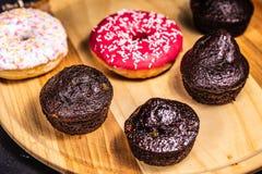 Met een suikerlaagje bedekte donuts en de muffins liggen op een houten plaat royalty-vrije stock foto