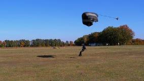 Met een valscherm vliegen en ter plaatse gelande Skydiver die Langzame Motie stock video