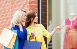 met en sac l'avant d'appareil-photo regardant au sujet des achats souriant deux femmes de vue jeunes Photo stock