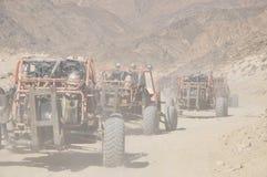 Met fouten in het konvooi die door de woestijn reizen Stock Fotografie