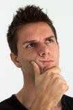 Met hand op gezicht denkt en mens die omhoog kijkt Stock Foto