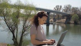 Met laptop door de rivier Meisje dat aan laptop werkt Het werk in de verse lucht stock footage