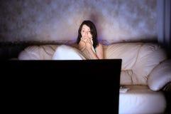 Met littekens bedekt mooi meisje dat op TV op een laag let Stock Foto's