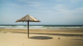 Met stro bedek paraplu op het strand Stock Foto's