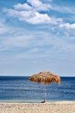 Met stro bedek paraplu's op het strand Stock Foto
