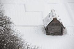 Met stro bedekt dakhuis dat in sneeuw in de winter wordt behandeld Stock Foto's