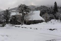 Met stro bedekt die dakhuis in sneeuw in de winter wordt behandeld Royalty-vrije Stock Afbeeldingen