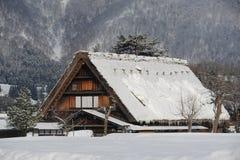 Met stro bedekt die dakhuis in sneeuw in de winter wordt behandeld Royalty-vrije Stock Foto's