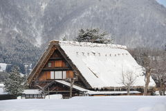 Met stro bedekt die dakhuis in sneeuw wordt behandeld Stock Foto's