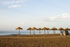 Met stro bedekt sunshades in een strand Stock Afbeelding