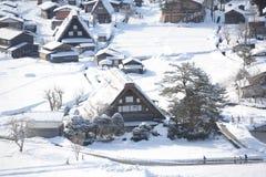 Met stro bedekte dakhuizen die in sneeuw worden behandeld Stock Foto