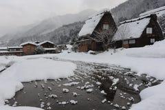 Met stro bedekte die dakhuizen in sneeuw in de winter worden behandeld Stock Foto