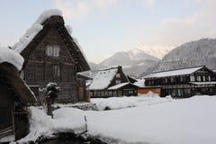 Met stro bedekte die dakhuizen in sneeuw in de winter worden behandeld Stock Afbeelding