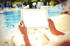 Met tabletzitting bij zwembad Royalty-vrije Stock Fotografie