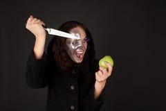 Met twee aangezichten heks met groen appel en mes Royalty-vrije Stock Afbeeldingen