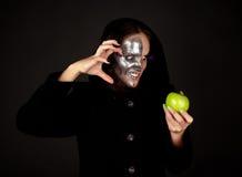 Met twee aangezichten heks met het groene appel grijnzen Stock Afbeelding