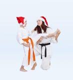Met zwarte en oranje riem in kappen van Santa Claus leidt de sportfamilie schopbeen op stock afbeeldingen
