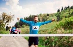 Meta do cruzamento do corredor do homem em uma competição da raça na natureza foto de stock